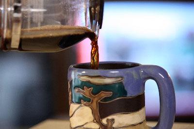 Coffee pouring into a clay mug